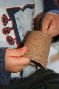 Little boy holding seed pots