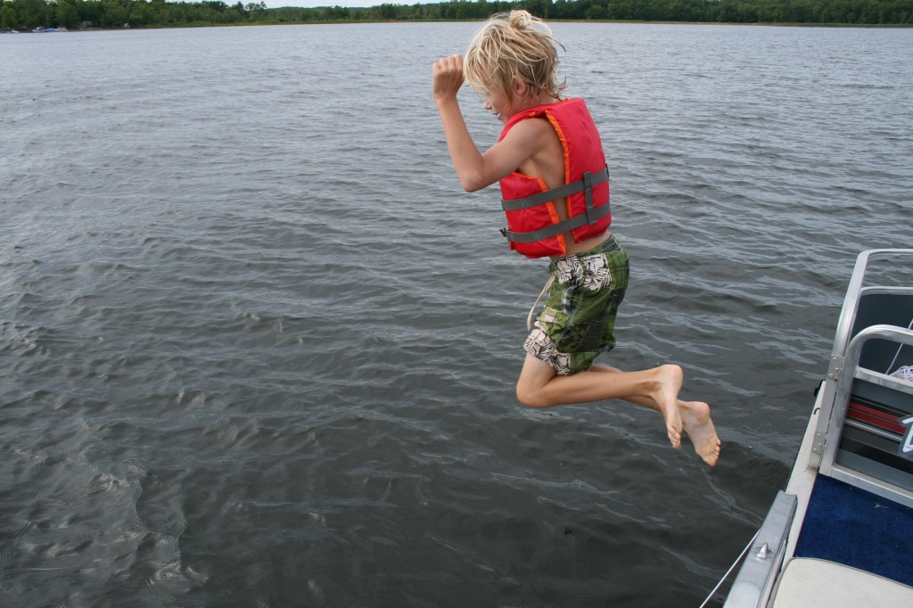Boy jumping into the lake