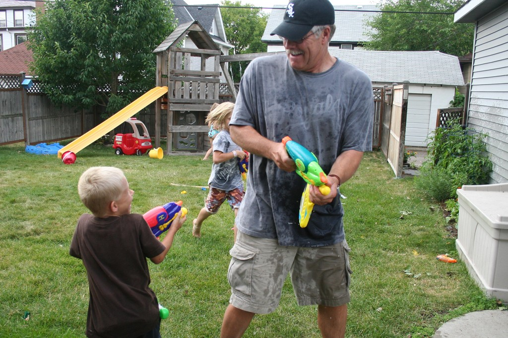 Kids playing water guns with Grandpa